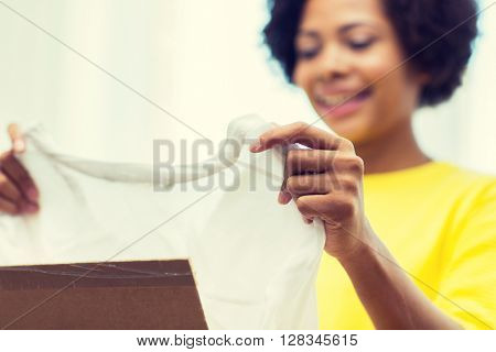 people, delivery, commerce, shipping and postal service concept - close up of happy african american young woman taking clothes out of cardboard box or parcel at home