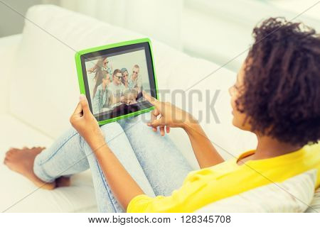people, technology, advertisement and leisure concept - happy african american young woman sitting on sofa and looking at picture on tablet pc computer screen at home