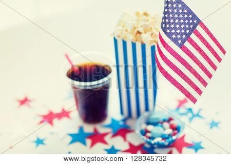 celebration, patriotism and holidays concept - close up of american flag, coca cola cup, popcorn and candies with stars confetti decoration at 4th july party on independence day