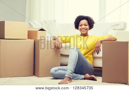 people, moving new place and repair concept - happy african american young woman with many cardboard boxes sitting on floor at home