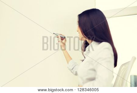 education, business and people concept - happy woman with marker writing on whiteboard