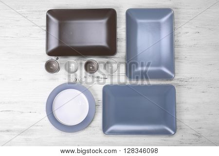 Empty dishes on white wooden background.