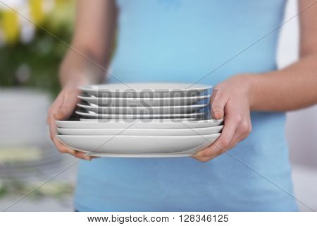 Woman holding stack of clean plates, close up