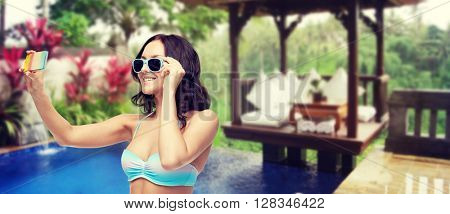 people, technology, summer holidays, travel and tourism concept - happy young woman in bikini swimsuit and sunglasses taking selfie with smatphone over hotel resort background