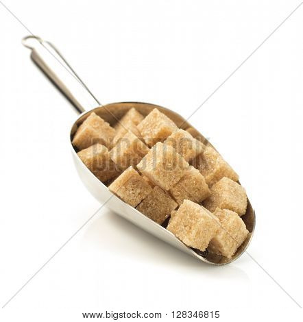 brown sugar cubes in scoop isolated on white background