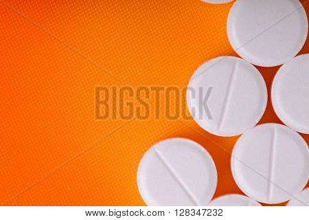 White pills on an orange background. Cocept of medical treatment