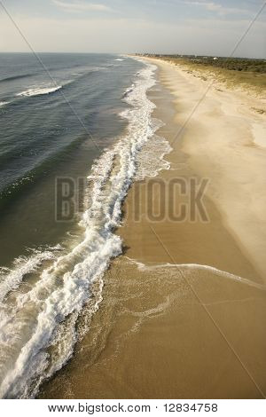 Aerial view of waves crashing on beach on Bald Head Island, North Carolina.