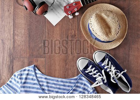 Guitar, headphones, music sheets and clothes on wooden surface, top view