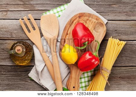 Cooking utensils and ingredients on wooden table. Top view