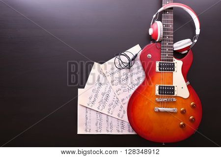 Electric guitar with notes and headphones on black wooden background
