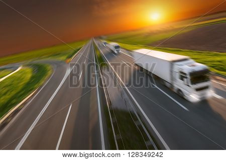 Three new reefer trucks in a row at left side driving on freeway with speed blurred motion. Freight scene on the motorway. Speed concept for temperature controlled truck.