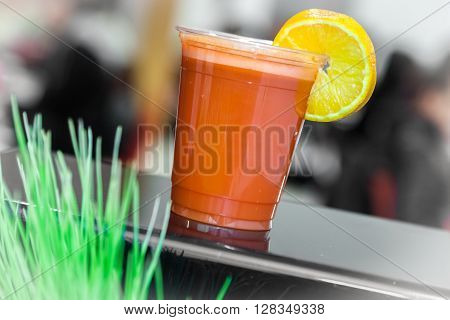 Orange and carrot smoothie in a plastic recyclable cup with a straw