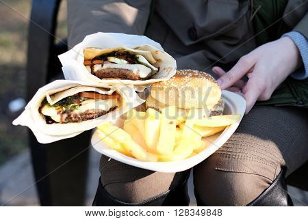 Street food. Woman holding hamburgers and french fries outdoors.