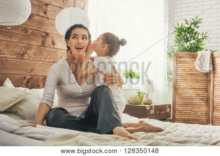 Happy loving family. Mother and her daughter child girl playing and hugging. Daughter whispering to mom a secret.