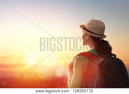 young beautiful woman looking at the city at sunset