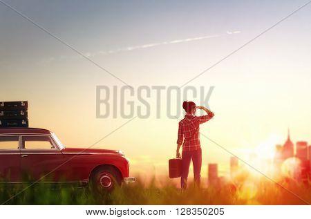 Toward adventure! Girl relaxing and enjoying road trip. Beautiful young woman looking on city.