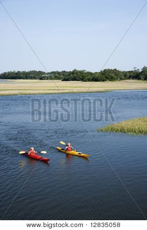 Two teenage boys kayaking through marshland on Bald Head Island, North Carolina.