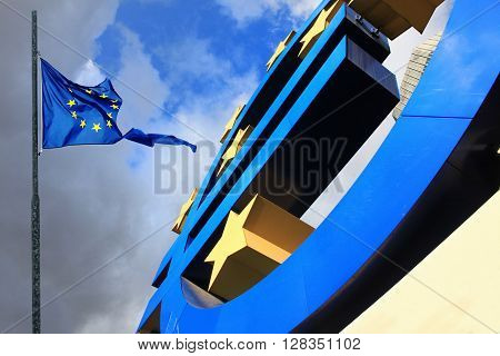 FRANKFURKT, GERMANY - DEC 17, 2011: Euro sign at European Central Bank headquarters in Frankfurt Germany 17 December 2011 with dark dramatic clouds symbolizing a financial crisis