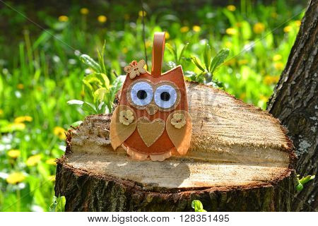Felt owl toy on a stump. Felt soft bird toy outdoor, kids crafts. DIY concept