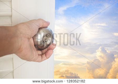 Hand opening door with beautiful sky, dreamy concepts