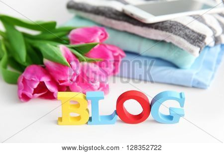 Word BLOG with stack of clothes, mobile phone and bouquet of fresh tulips closeup