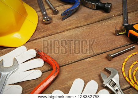 Working tools and yellow helmet on a wooden background.