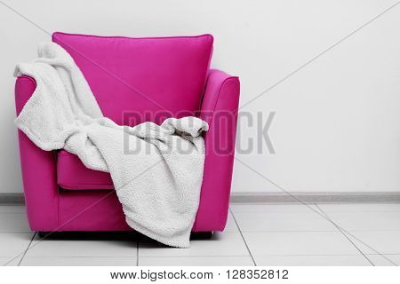 Pink armchair with blanket on light wall background