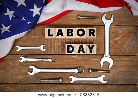 Labor day concept. Different kinds on wrenches and wooden cubes on table.
