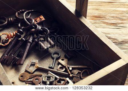 Wooden box full of old keys closeup