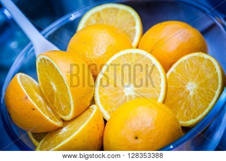 Cut in half oranges in a glass bowl about to be used in a healthy smoothie