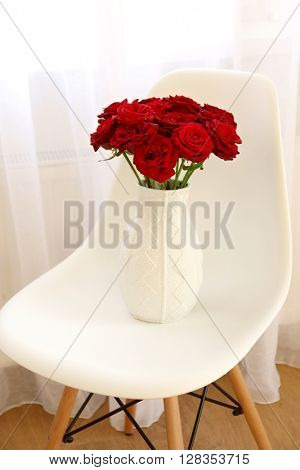 Red roses on chair beside window with curtain