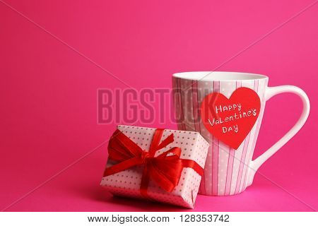 Cup with greeting card and gift box for Valentines Day on pink background
