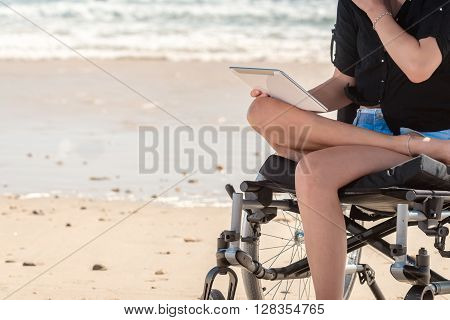 Young woman in wheelchair using tablet at the beach
