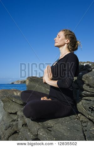Caucasian mid-adult woman practicing yoga on rocky coast of Maui, Hawaii.