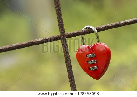 Red padlock in the shape of a heart fixed to a rusted concrete wire construction