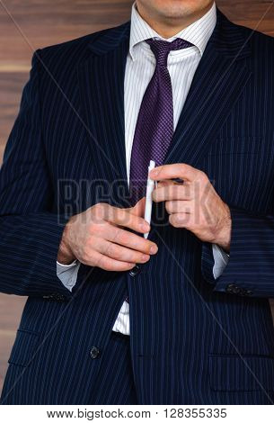 Confident businessman executive abstract portrait holding white pen in hands lying next to luxury wooden wall in his modern office