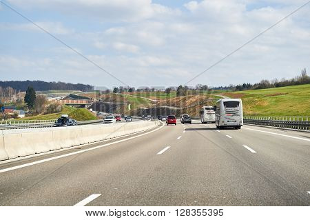 GERMANY - MAR 26 2016: Bundesautobahn or Federal Motorway highway with busy traffic on a spring day with beautiful green fields and blue clouds