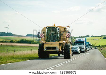 FRANCE JUL 11 2011: Large agricultural Machine - Special Transport driving on French road with traffic jam behind