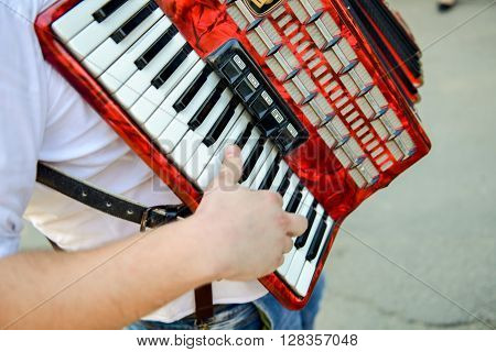 Man playing on a electronic accordion in natural light ** Note: Soft Focus at 100%, best at smaller sizes