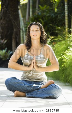 Pretty young adult Caucasian brunette woman sitting in lotus position practicing yoga with hands at heart center.