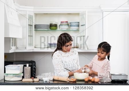 Mother and daughter making dough for the cake