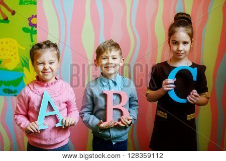 three happy prescholler children with abc letters selective focus