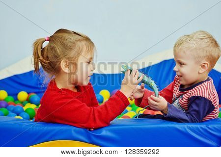 two children playing in pool with balls