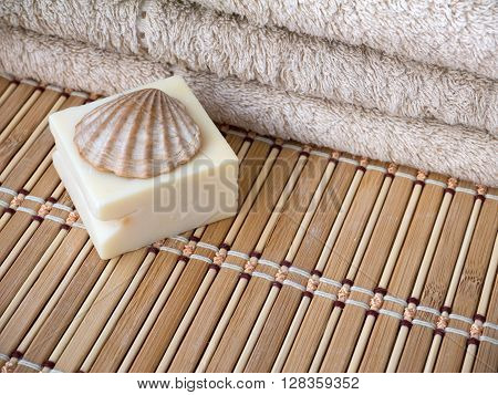 Natural milk soap bar scallop shell and terry towel on the bamboo mat