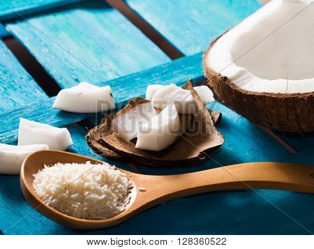 Half coconut with wedges of coconut and shredded coconut on bright blue wooden background. Angle view, copy space