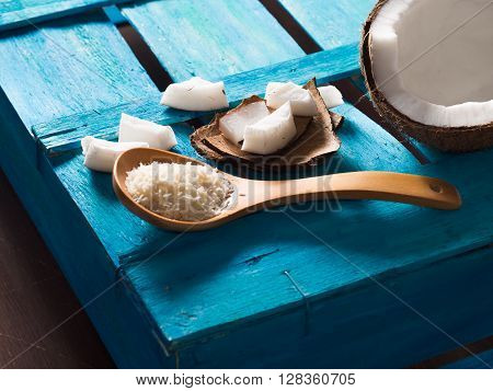 Half coconut with wedges of coconut and shredded coconut on bright blue wooden background