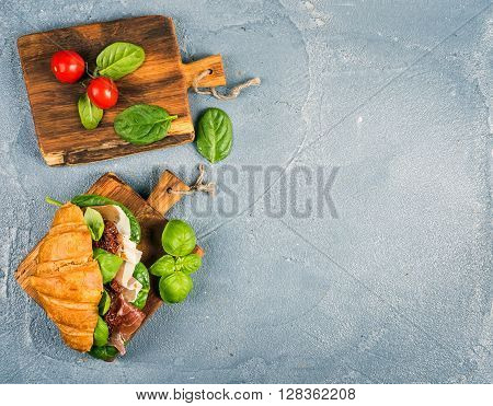 Croissant sandwich with smoked meat Prosciutto di Parma, sun dried tomatoes, fresh spinach and basil on small rustic wooden boards over stone textured grey background, top view, copy space