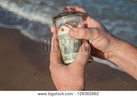 male hands holding a glass jar with money and shells found on the shore of the sea