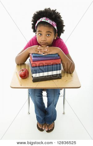 African American girl sitting at school desk with large stack of books looking up at viewer.