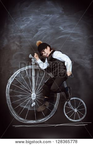 Elegant boy in a suit, bowler hat and glasses posing by a painted retro bicycle. Old Europe style, England. Little gentleman. Kid's fashion.